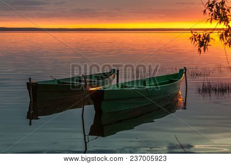 Two Wooden Boats Against The Background Of Bright Sunset Paints