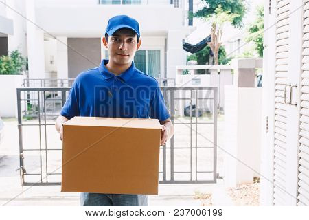 Delivery Man With Cardboard  Box Near House Of Customer