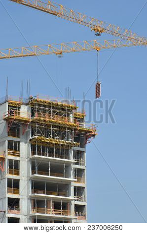 Modern Building With Workers And A Crane Under Construction