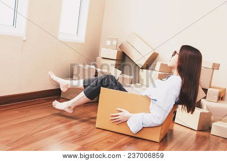 Young Woman Sitting In A Cardboard Box At Home