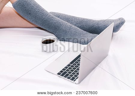 Woman Legs In Knee Socks With Notebook And Cup Of Coffee On White Bed At Home