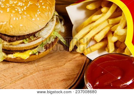 Delicious Big Hamburger With French Fries And Ketchup On Wooden Table