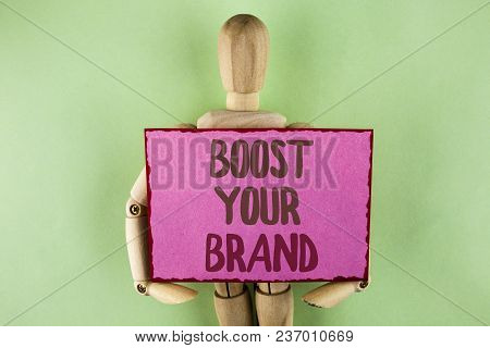 Handwriting text writing Boost Your Brand. Concept meaning improve your models name in your field overcome competitors written Sticky note paper holding by Wooden Robot Toy on plain background. poster
