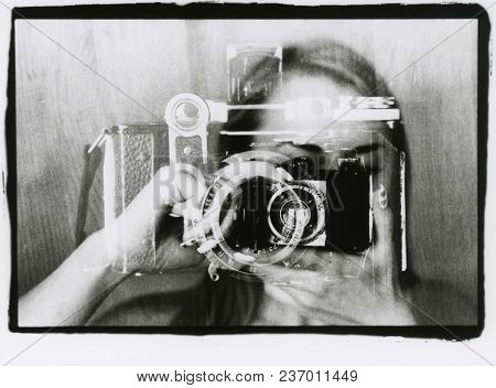 The Girl Is Looking Into The Viewfinder Of A Rare Camera. Multiple Exposure. Attention! The Image Co