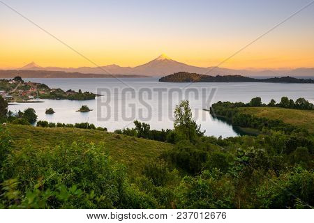 View Of Puerto Octay At The Shores Of Lake Llanquihue, With Osorno Volcano And Puntiagudo Volcano In