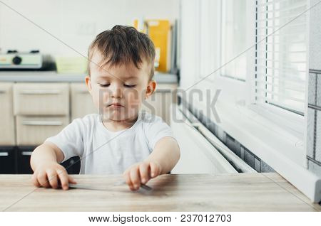 Child Sits At The Table And Takes A Fork, On The Table There Is Nothing