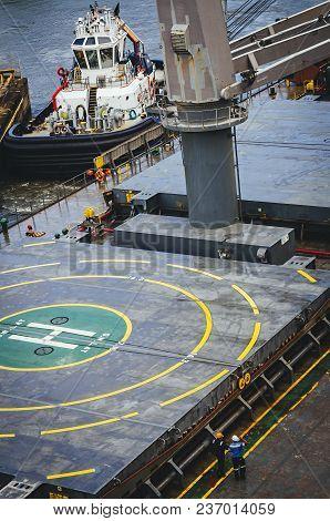 Tugboat Maneuvering Pulls A Ship With Helipad Area On The Bridge