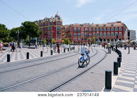 NICE, FRANCE - JUNE 4, 2017: A view of the Place Massena square in Nice, France, with the tramway rails in the foreground. This is the main public square in the famous city of the French Riviera