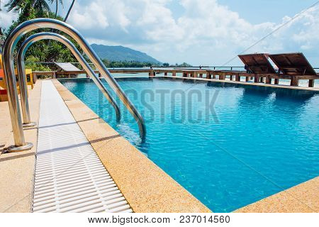 Swimming Pool With Stair And Stone Deck At Hotel. Sea View.