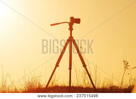 Silhouette of camera on tripod on sunset background. Shooting rural landscape at sunset