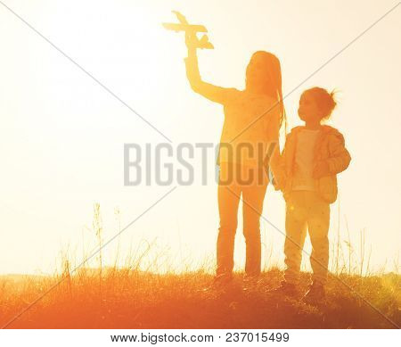 Two little sisters holding hands and playing with small airplane toy outdoors. Silhouette of two sisters walking on the meadow at sunset
