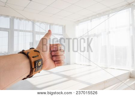 Male hand with brown leather bracelet showing thumbs up sign against white background. Man's hand showing thumbs up in front of light big windows, copy space