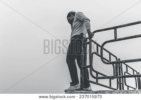 Depressed And Upset Man Is Going To Jump From Bridge Standing On Edge. Suicide Concept, Black And Wh