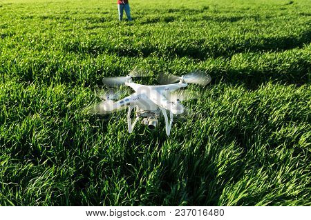 Russia, Rostov-on-don - April 20, 2017: White Low-flying Drone, On The Background Of Green Grass And