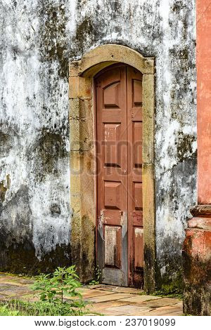 Old And Aged Historic Wooden Church Door In The City Of Ouro Preto, Minas Gerais With A Stone Frame
