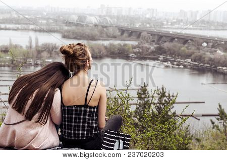 Two Girls Have A Rest Sitting On The Slope Of A High Mountain In The Afternoon