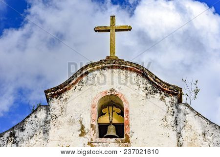 Bell And Crucifix On Top Of Old Chapel In The Historic City Of Ouro Preto In Minas Gerais With Blue