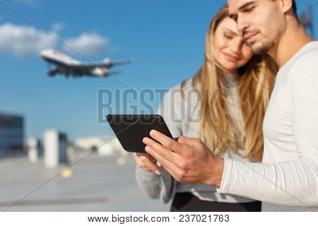 Young Couple Booing Flight On Digital Tablet Outdoor, Buying Air Ticket