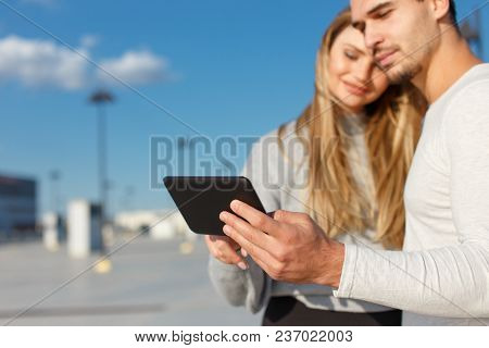 Young Couple Using Digital Tablet Outdoor, Depth Of Field
