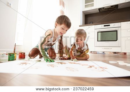 Two Brothers Paint With Gouache On A Large Sheet Of Paper, Which Lies On The Floor.