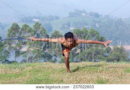 Indian Fighter Doing Exercises With Sword During Kalaripayattu Marital Art Demonstration In Kerala,