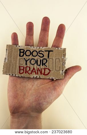 Writing note showing  Boost Your Brand. Business photo showcasing improve your models name in your field overcome competitors written Tear Cardboard Piece placed Hand the plain background. poster