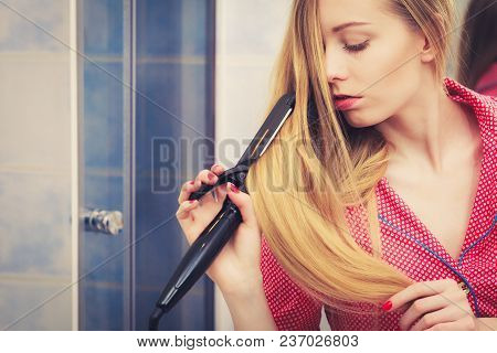 Haircare And Hairstyling Concept. Woman Straightening Her Long Blond Hair Using Straightener Tool.