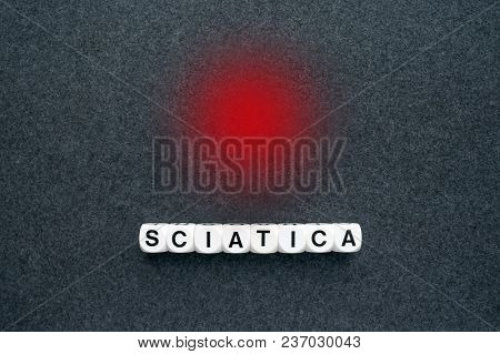 Word Sciatica From White Blocks And Red Circle Dot On Dark Fabric Background. Orthopedics, Neurology