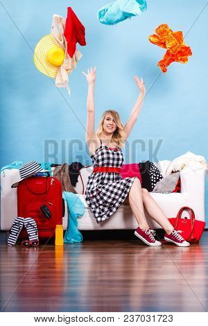 Cleaning In The Closet, Packing For Travel, Fashion, Happiness Concept. Woman Sitting On Sofa Throwi