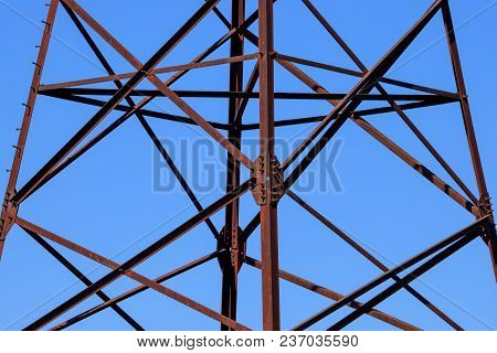 Rusty Metal Construction Of A Power Line Support Close-up Against A Blue Sky Background