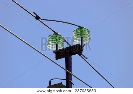 Glass Insulators Of A Transmission Line Supports Close-up On Blue Sky Background