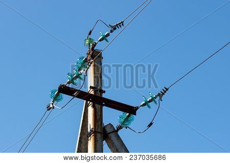 Concrete Pillar Of A Power Transmission Line With Wires Close-up Against A Blue Sky