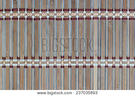 Thin Wooden Plank Bound With Colored Threads. Abstract Wooden Background