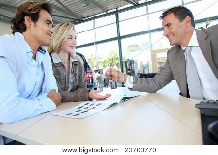 Car seller giving car key to buyers
