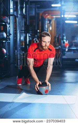 Muscular Beards Man Doing Intense Core Workout In Gym. Doing Core Exercise On Fitness Mat With Medic