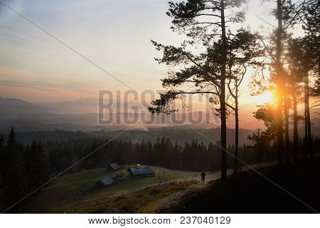 Sunrise Above The High Mountain Foggy Valley With Old Wooden Houses On A Hill