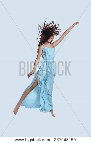 Magic! Full Length Studio Shot Of Attractive Young Woman In Elegant Dress Gesturing While Hovering A