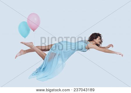 Dream Fly. Studio Shot Of Attractive Young Woman In Elegant Dress Keeping Arms Outstretched While Ho