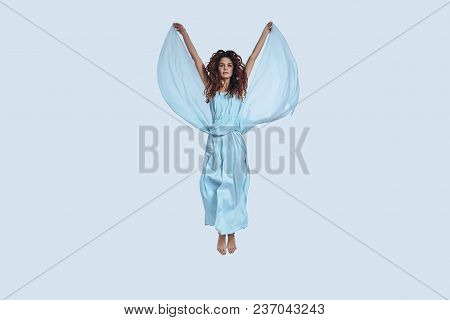 Zero Gravity. Full Length Studio Shot Of Attractive Young Woman In Elegant Dress Looking At Camera W