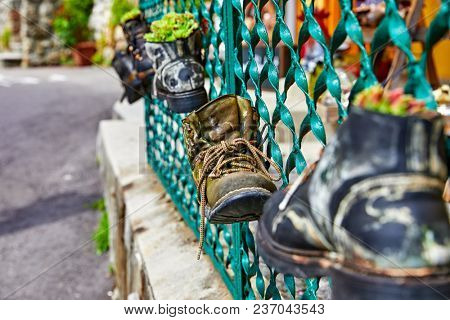Old battered boots with lace rope used as decorations for shabby metal fence.