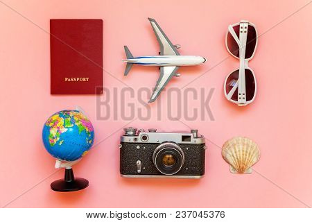 Flat Lay With Plane, Vintage Camera, Passport, Sunglasses, Globe And Shell On Pink Colourful Pastel