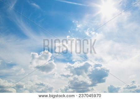 Beautiful Colorful Blue Sky With White Fluffy Clouds And Bright Sun Light Background. Horizontal Col