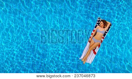Summer Vacation. Enjoying Suntan Woman In Bikini On The Inflatable Mattress In The Swimming Pool.