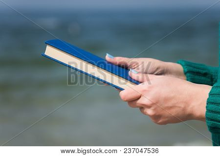 Closeup Of White Female Hands  Holding Thick Paper Book In Hands Isolated At Blurry Blue Sea Backgro