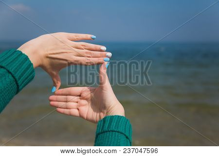 Closeup Of Female Caucasian Hands Isolated On Blue Background. Young Woman Forming Frame With Her Tw