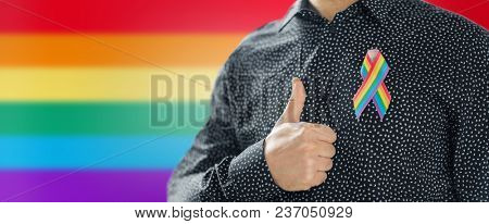 lgbt, same-sex relationships and homosexual concept - close up of man with gay pride awareness ribbon on his chest showing thumbs up over rainbow background