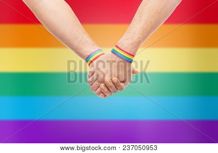 lgbt, same-sex relationships and homosexual concept - close up of male couple wearing gay pride awareness wristbands holding hands over rainbow background