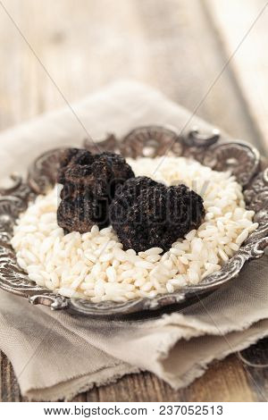 Black Truffles And Rice On Plate  On Old Wooden Table.