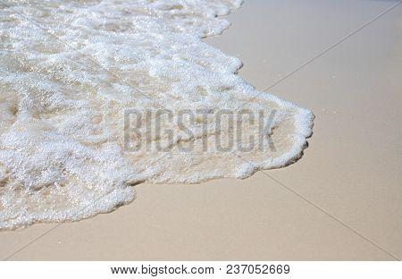 Sea Wave On Sand Beach Photo Background. Coral Beach Sand With Sea Wave. White Sand Of Oceanic Coast