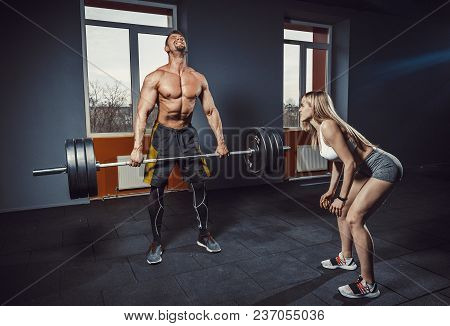Fit Woman Motivates Man While He Doing Deadlift With Heavy Barbell. Man Lifting Barbell Opposite Win